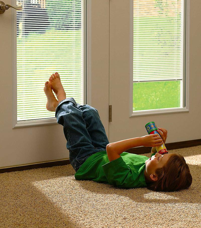 boy laying on floor with feet on window in door with Add-On blinds