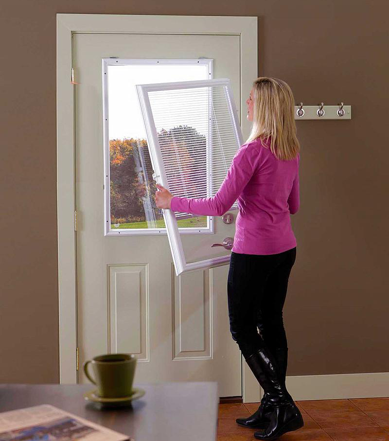 lady in pink shirt hanging a window sized add-on blind to her door