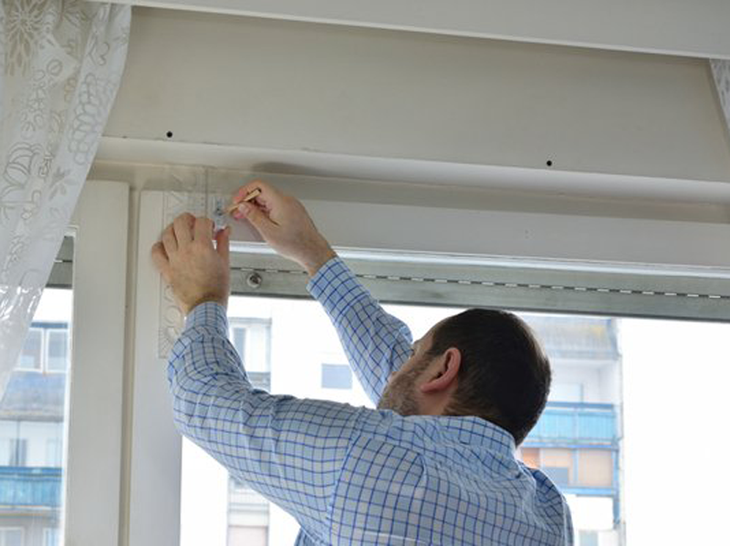 man fixing clips on window blinds