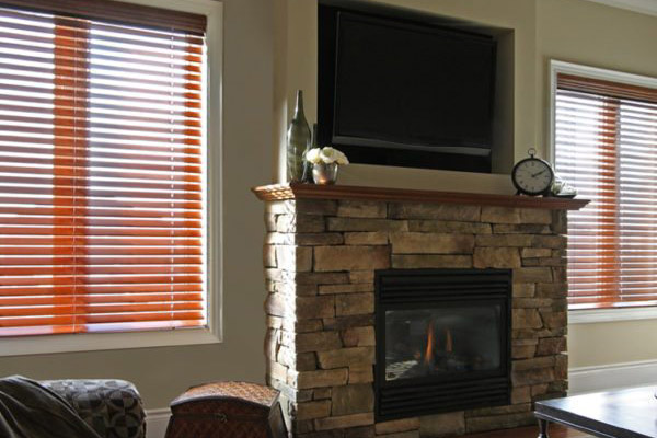 brown horizontal blinds on a beige wall with fireplace in between